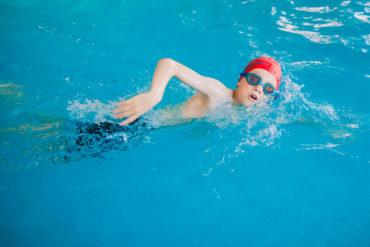 Niño nadando que debe cuidar sus oídos
