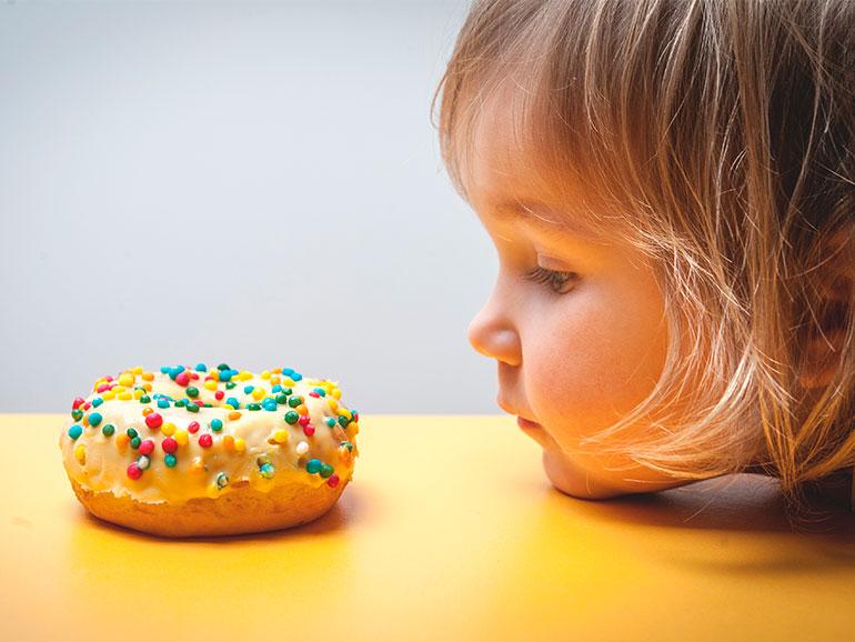 Niña con obesidad mira un pastel