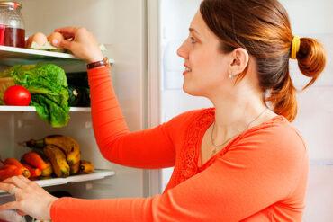 Mujer revisando alimentos en refrigerador