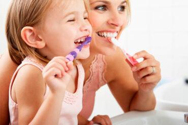 niña lavándose dientes con mamá